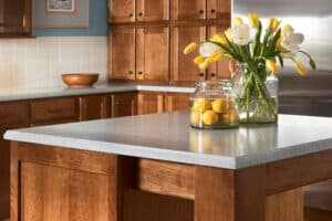kitchen island with light gray granite countertops with jar of lemons and yellow flowers
