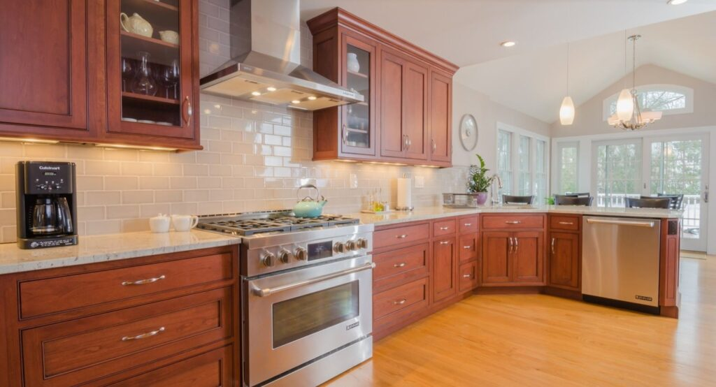 kitchen with cherry wood cabinets, stainless steel appliances, light oak flooring, light stone countertops, and a white subway tile backsplash