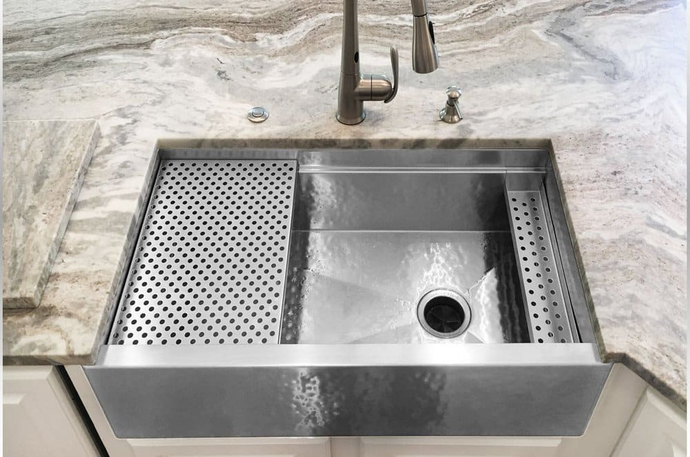 havens hammered metal sink set under a wavy grey/brown granite countertop atop white cabinets