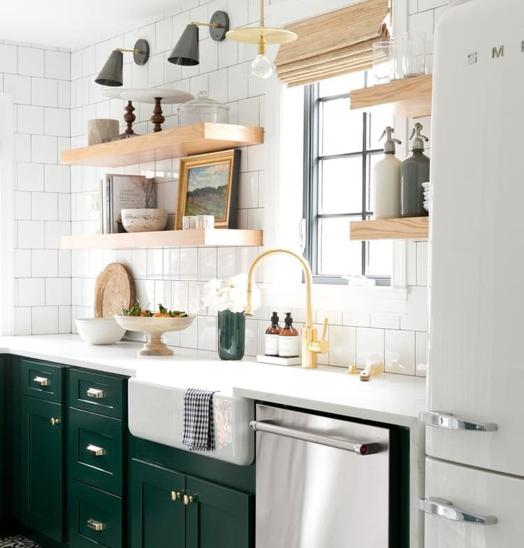 remodeled kitchen with white subway tile and mixed materials throughout - light wood, white solid surface counters, gold fixtures, stainless steel appliances, and forest green cabinets
