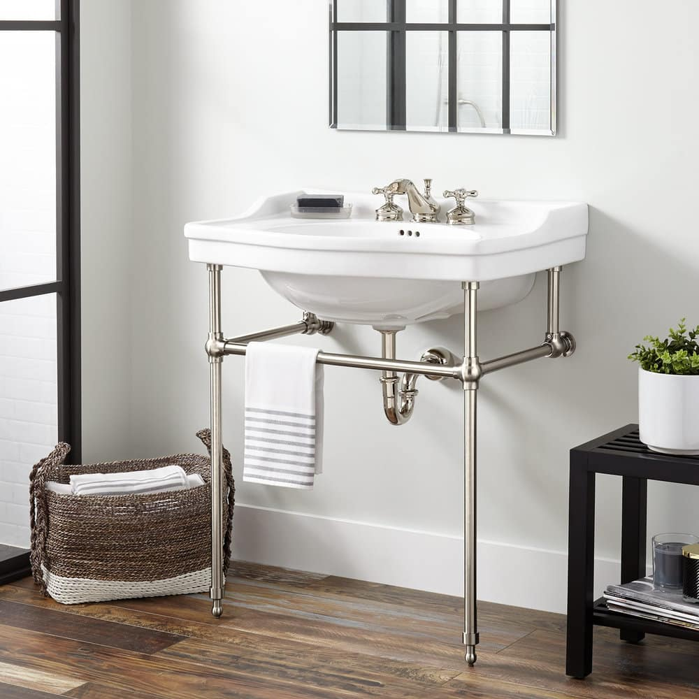 remodeled bathroom with industrial looking white console sink with exposed plumbing and stainless steel pipes as vanity legs
