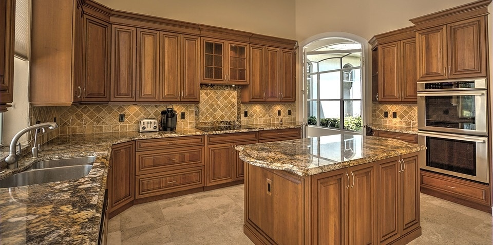 remodeled kitchen with medium brown wooden cabinets, brown granite countertops, and light brown tile floor and backsplash