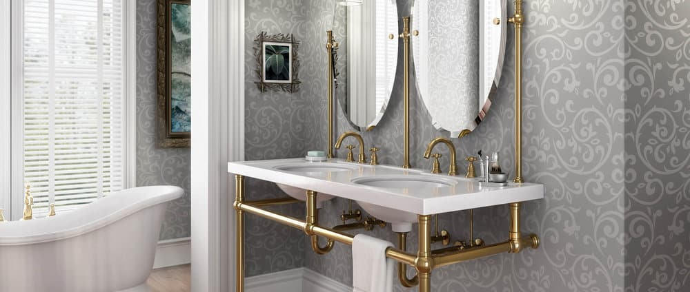 remodeled bathroom with patterned grey wallpaper, soaking tub by a window, ornate white molding and trim, and a white console sink with exposed brass plumbing and brass pipes for vanity support