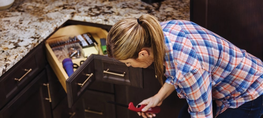 woman holding candle lighter next to kraftmaid corner cabinet with open corner drawer