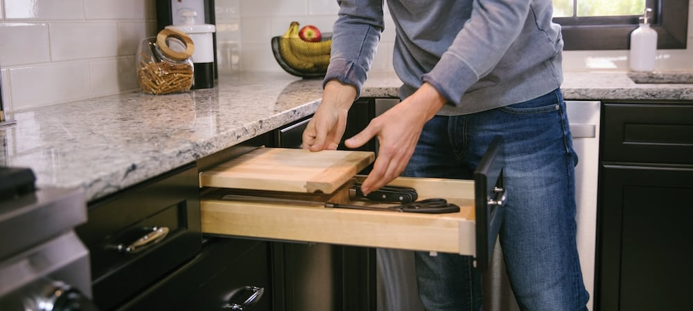man in kitchen extending cutting board from kraftmaid cabinet drawer