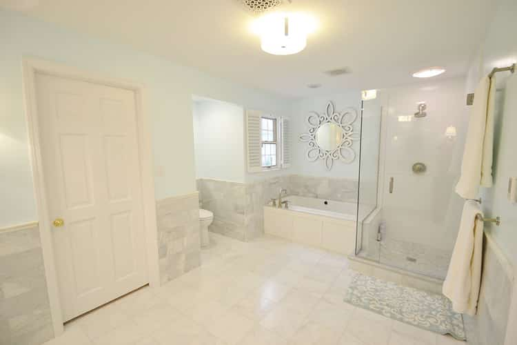 light and bright spa-like remodeled bathroom with white and grey marble floors, a tub, and glass shower