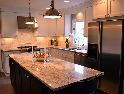 remodeled kitchen with two-tone cabinets, white and grey granite countertops and backsplash, island pendant lights, and stainless steel appliances