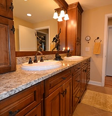 remodeled bathroom vanity with medium wood cabinets, light stone countertop, and white sink with antique bronze fixtures